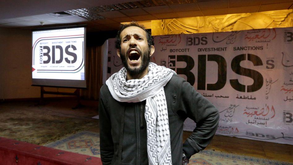 Mann vor BDS-Plakat in Kairo, Ägypten