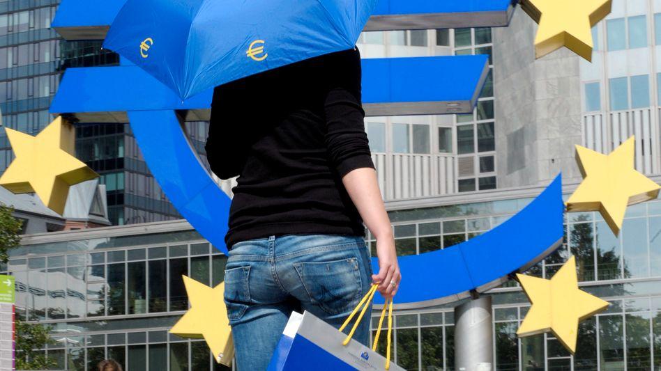 Frau mit Regenschirm vor der Europäischen Zentralbank (Symbolbild)