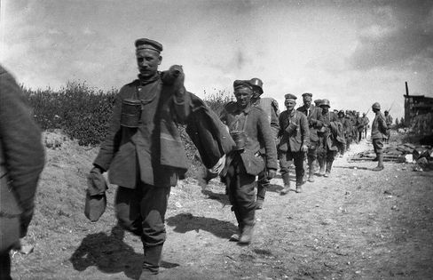 A column of German prisoners walk under the watch of French soldiers in Belgium in September 1918 at the end of World War I after the Allied victory.