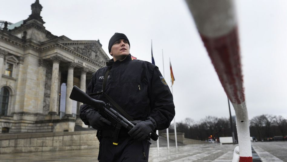 A police officer patrolling the fenced-off Reichstag parliament building in Berlin following the recent terror alert by the German government.