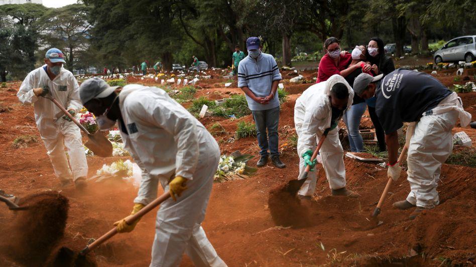 Friedhofsmitarbeiter und Angehörige eines Verstorbenen in São Paulo