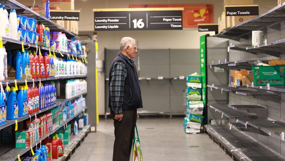 Ein älterer Mann steht beim Einkaufen in einem Woolworths-Supermarkt vor einem fast leeren Regal.