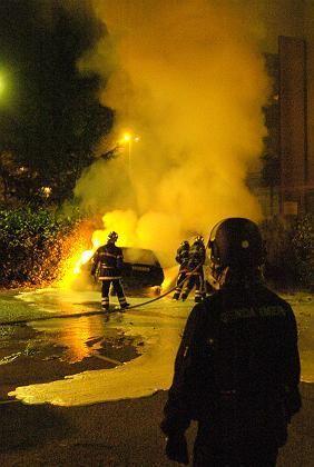 Firefighters extinguishing a burning car near Lyon on Sunday.