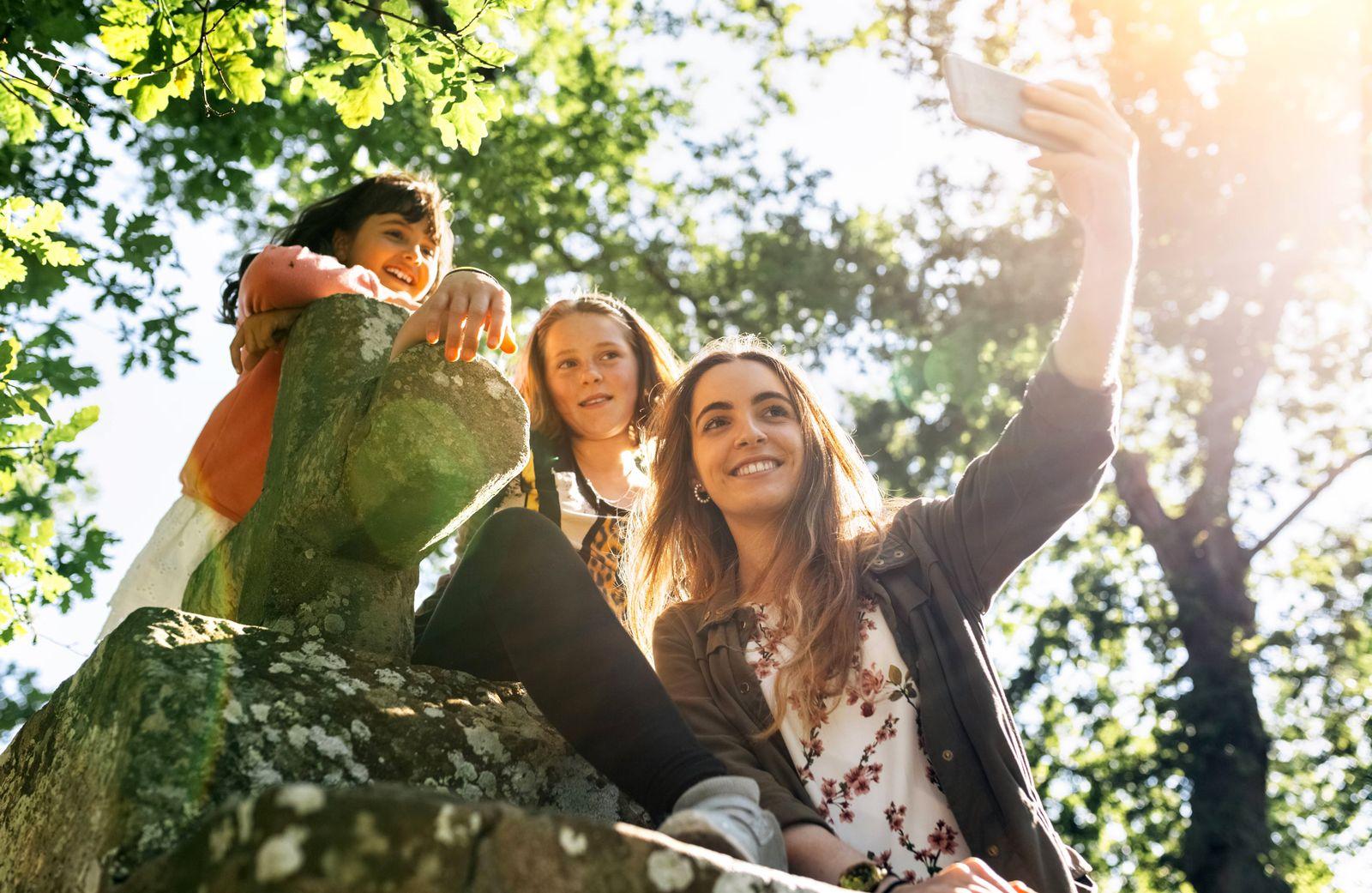Three happy girls taking a selfie outdoors model released Symbolfoto PUBLICATIONxINxGERxSUIxAUTxHUNx