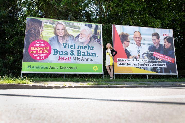 Die gewählte Landrätin Anna Kebschull zwischen den Wahlplakaten von sich und ihrem Gegner