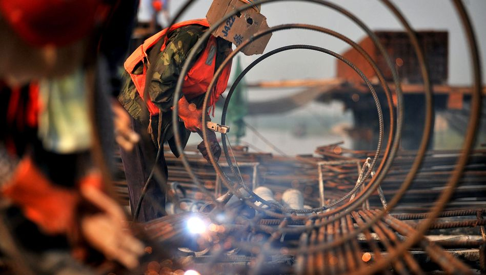Chinese workers welding steel at a construction site.