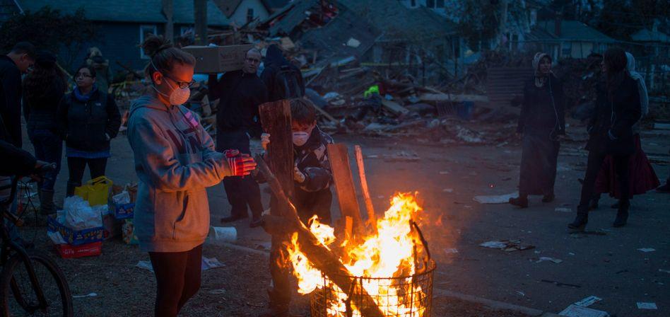 Feuer zwischen Trümmern: Eine Bewohnerin von Staten Island wärmt sich