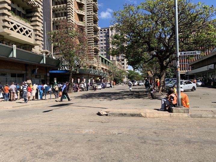 Menschen stehen an der Mugabe Road vor einer Bank Schlange