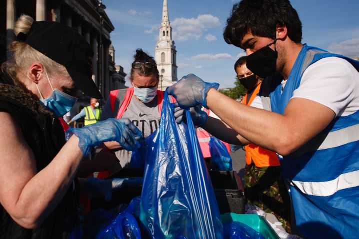 Freiwillige packen am Trafalgar Square in London Essenspakete in Einkaufstüten