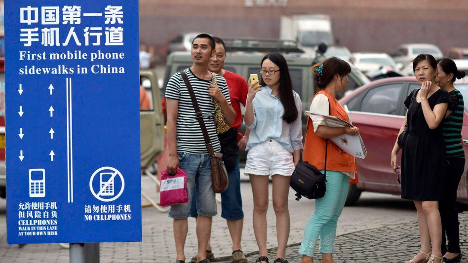 Chinas erster Smartphone-Fußweg: Fußgänger, die auf Handys starren