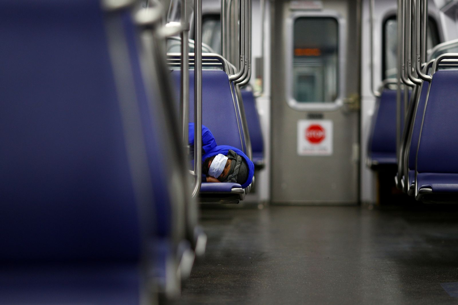 A person rests on a Washington Metro subway car wearing a face mask, following Mayor Muriel Bowser's declaration of a state of emergency due to the coronavirus disease (COVID-19) in Washington