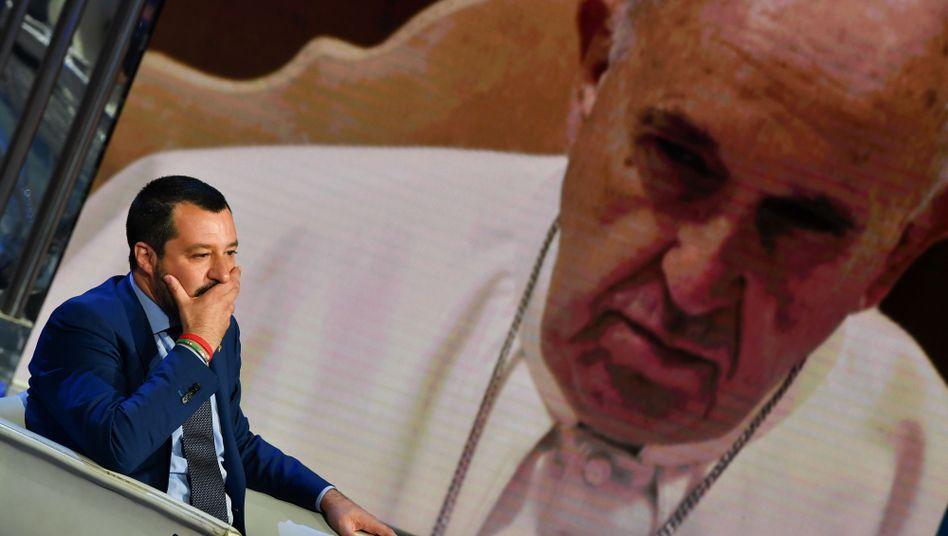 """Minister Salvini vor einer Leinwand mit dem Gesicht des Papstes: """"Katholiken am Scheideweg"""", titelt eine Zeitung"""