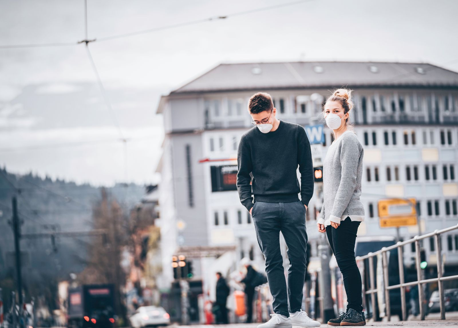 Young couple wait for train to arrive in ghost town