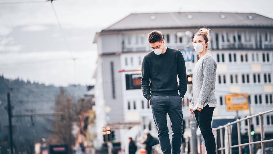 Junge Leute mit Schutzmasken