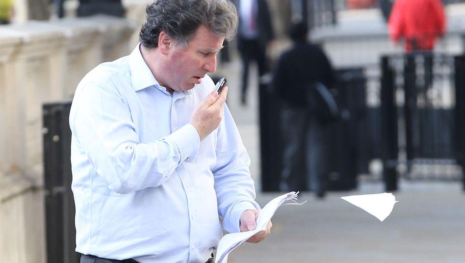 Staatsminister Oliver Letwin: Handy an einem Ohr, Papiere in der anderen Hand