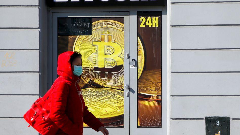 Frau mit Schutzmaske im polnischen Krakau: Wie schlägt sich Bitcoin in der Krise?