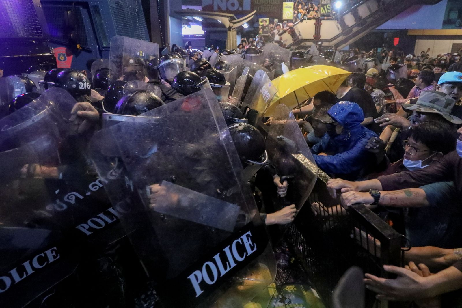 People scuffle with police officers during anti-government protests, in Bangkok