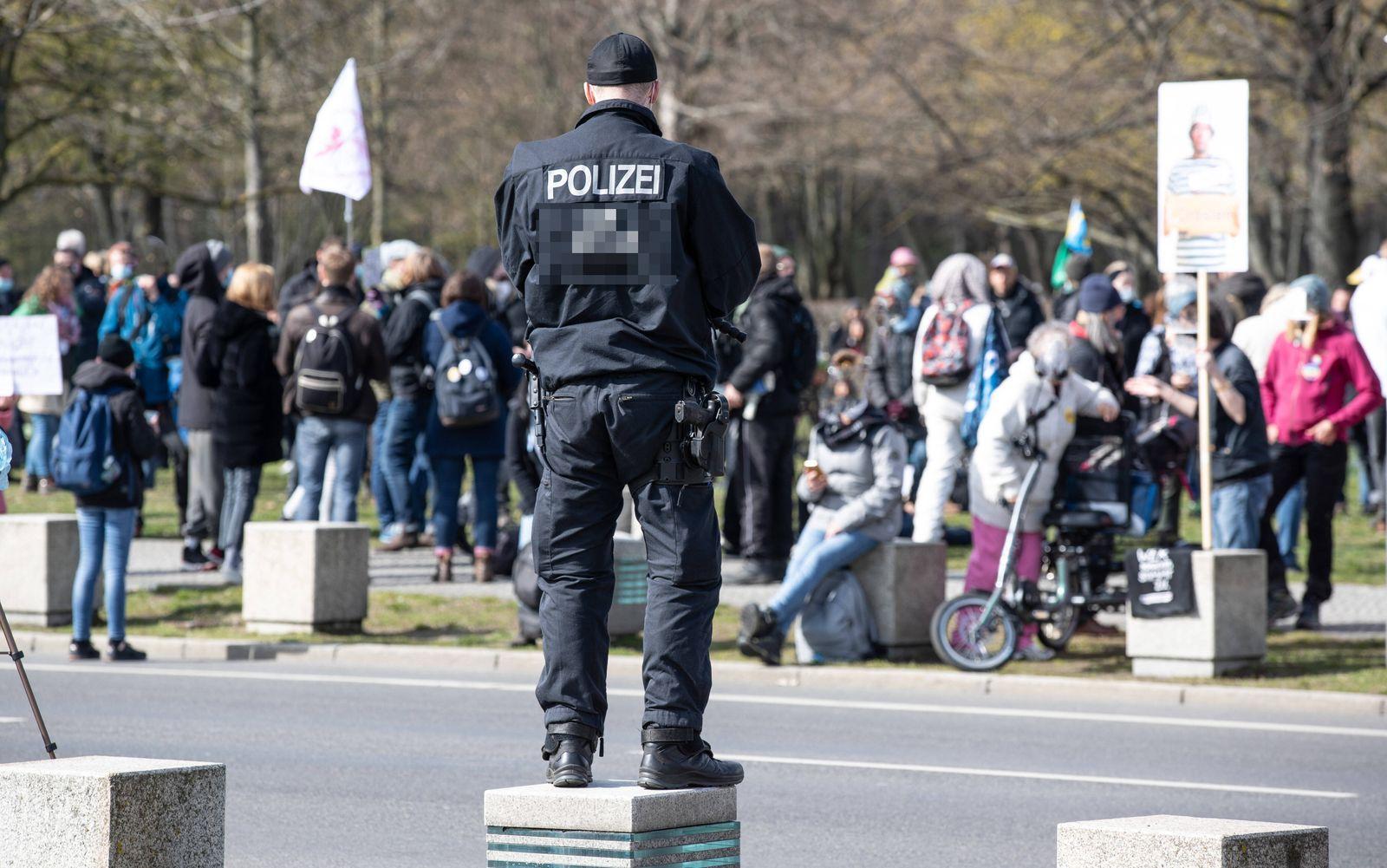 Berlin Demo Querdenker Corona Berlin, 13.04.2021, Regierungsviertel. Polizist bewacht eine Gruppe Demonstranten der Que