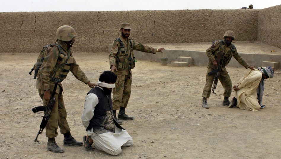 A photo released by Pakistan's intelligence services shows army troops seizing Taliban militants while on an offensive in the tribal district of South Waziristan in November.