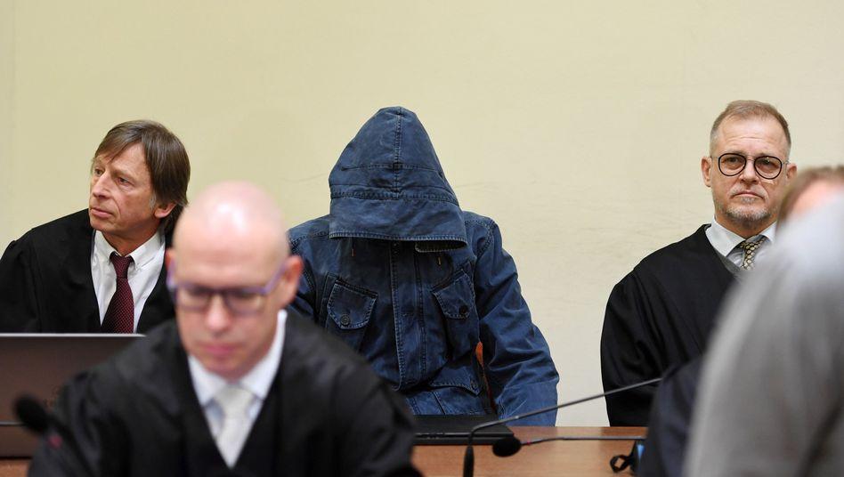 Carsten S. (mit Kapuze) mit seinen Anwälten Johannes Pausch (l.) und Jacob Hösl (r.)