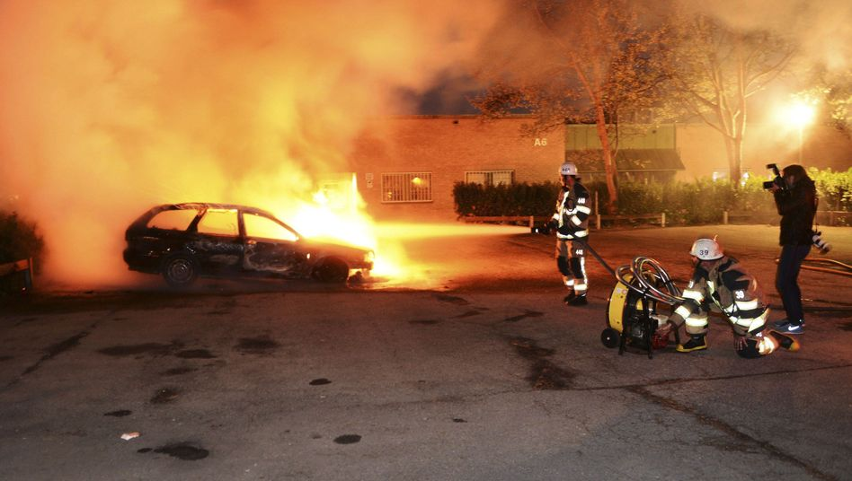 Firefighters extinguish a burning car after riots in the Stockholm suburb of Kista on May 21.