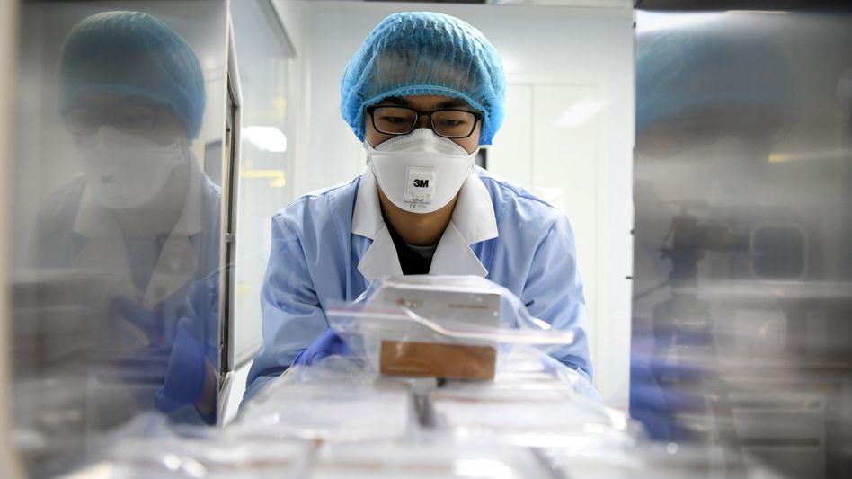 Ein Forscher liefert in China Flüssigkeiten an, mit denen sich das neue Coronavirus nachweisen lässt