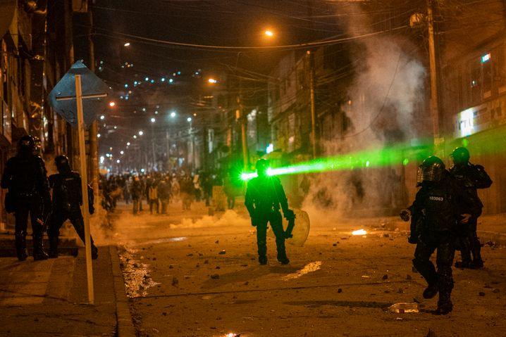 Ein Laserstrahl trifft einen Polizisten bei Protesten in Bogotá
