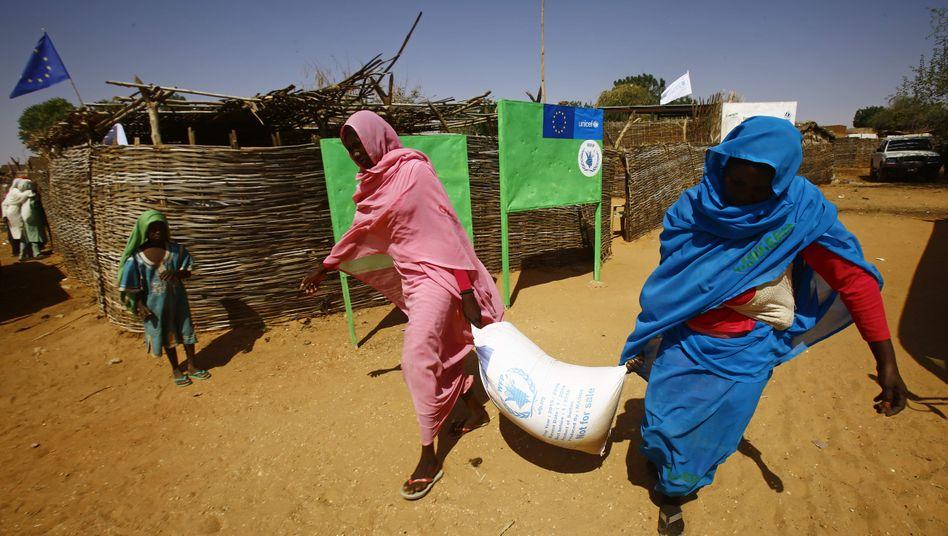Zwei Frauen im Lager für Binnenvertriebene in El Geneina tragen einen Sack mit Hilfsmitteln (Symbolbild)