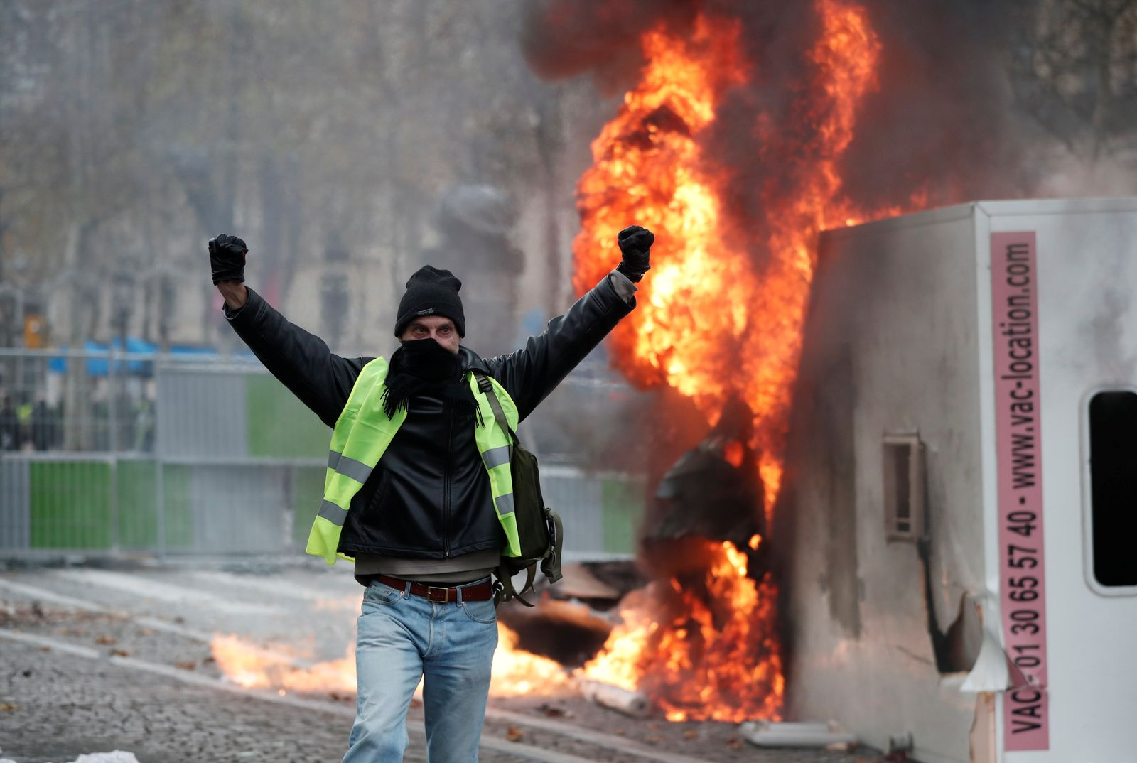 A protester wearing yellow vest, a symbol of a French drivers' protest against higher fuel prices, gestures during riots on the Champs-Elysees in Paris