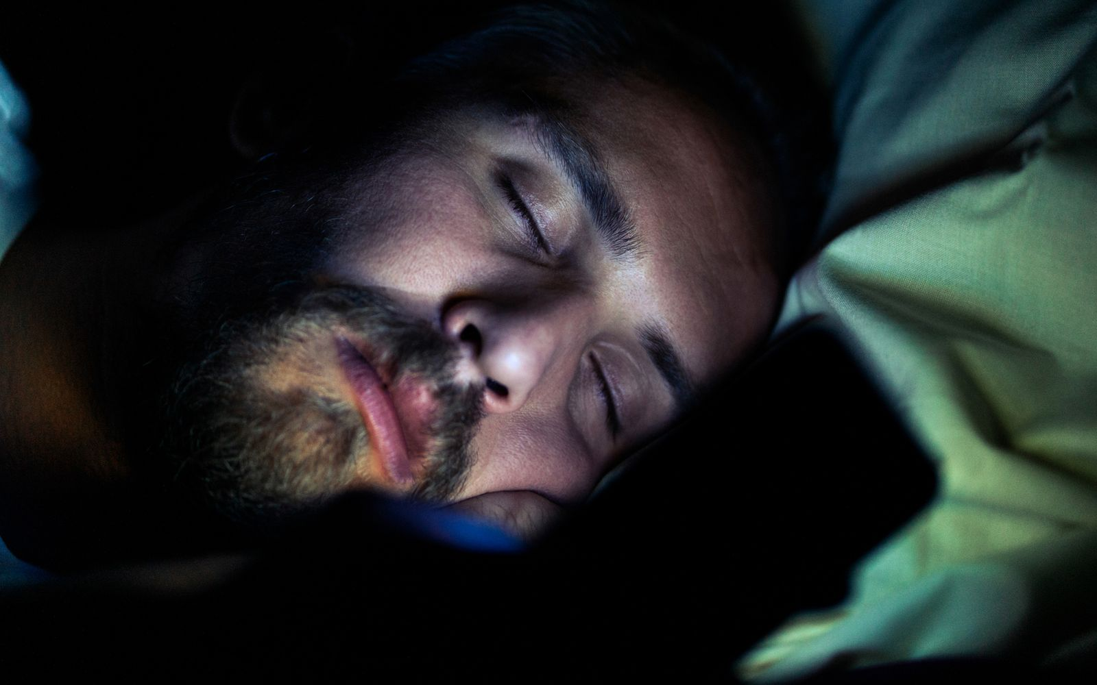 Bearded tired man in bed at night. He is watching something on phone