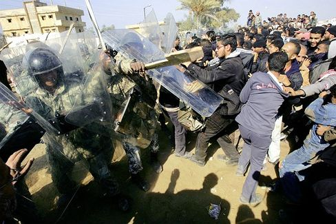 Egyptian border guards and riot police officers clash with Palestinians trying to cross the border between Egypt and the Gaza Strip in the border town of Rafah.