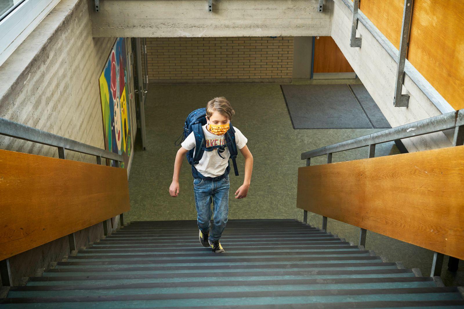 Boy wearing mask in school walking up stairs model released Symbolfoto property released DIKF00510