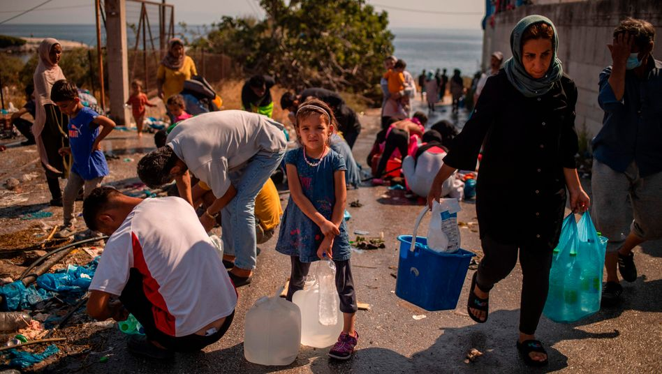 Ein Mädchen wartet darauf, ihre Kanister mit sauberem Wasser zu füllen: Beim Brand in Moria wurden Tausende Menschen obdachlos
