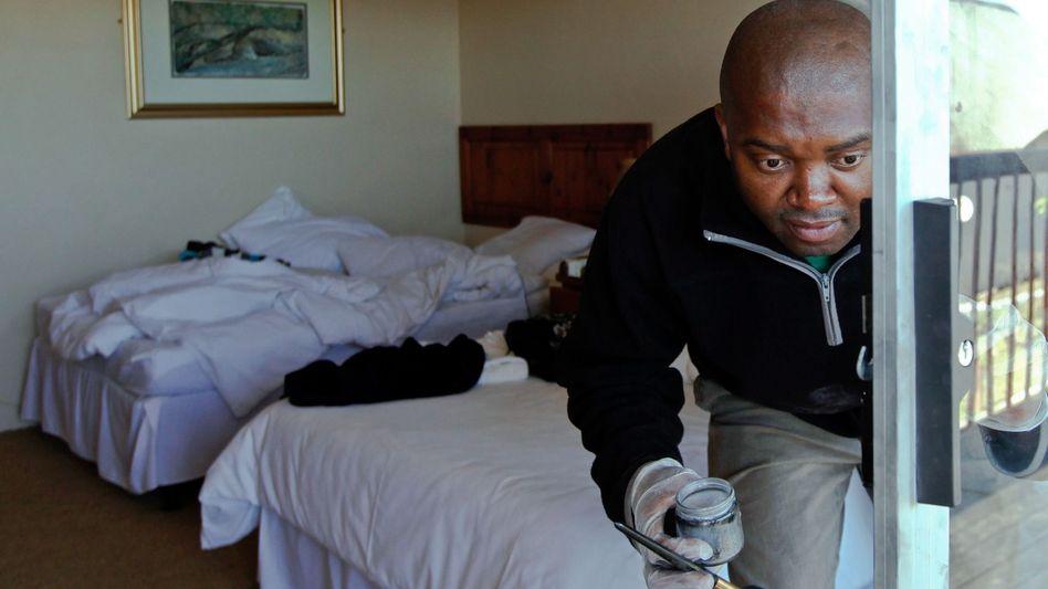 Ein Polizist sucht in der Nutbush Boma Lodge in Magaliesburg nach Fingerabdrücken.
