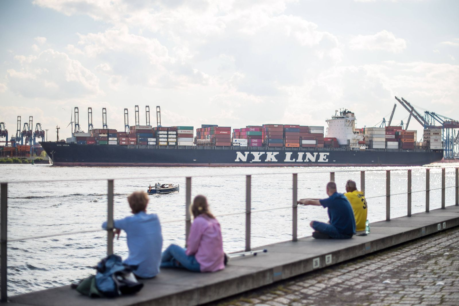 Hamburg Hafen Menschen sitzen bei sonnigem Fruehlingswetter im Hamburger Hafen und geniessen das gute Wetter. Im Hinterg