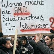 """Alevi Muslims protest in Cologne by the thousands against a TV show on the German channel ARD. """"Why is ARD spreading propaganda for Islamists?"""" reads the placard."""