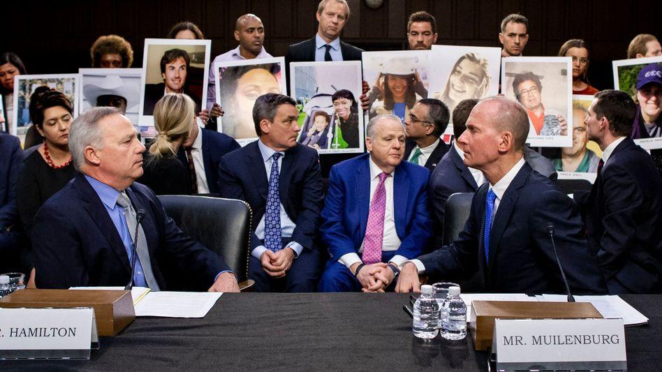 Boeing-CEO Muilenburg (r.) vor der Anhörung - dahinter Angehörige, die Fotos von Absturzopfern zeigen