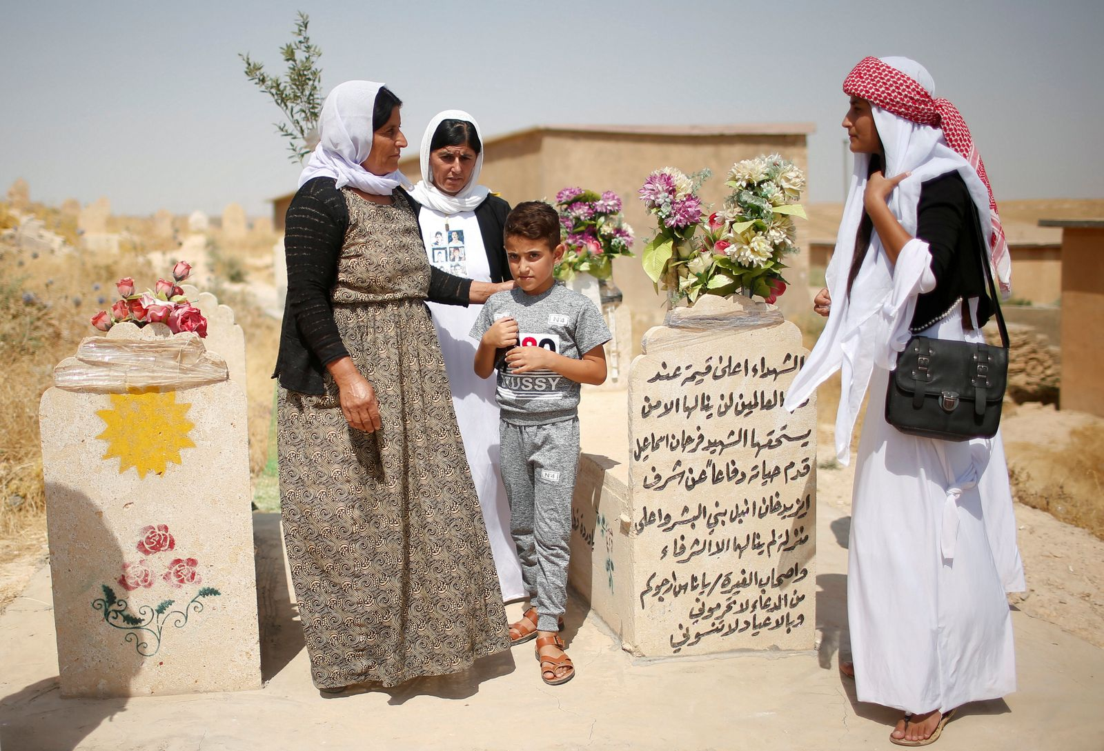 Yazidis visit a cemetery during a commemoration to mark three years since Islamic State launched what the United Nations said was a genocidal campaign against them in Sinjar region