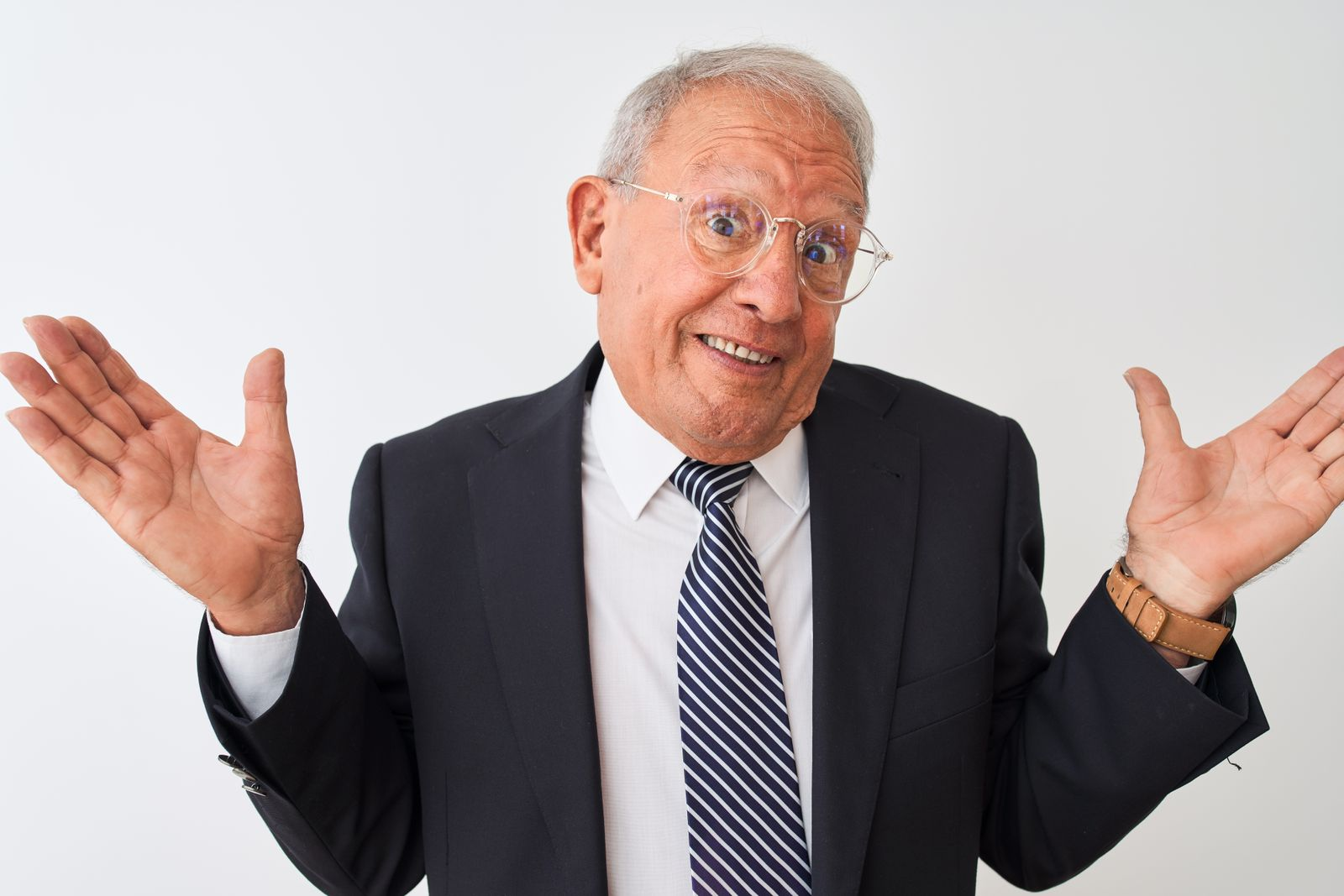 Senior grey-haired businessman wearing suit and glasses over isolated white background clueless and confused expression with arms and hands raised. Doubt concept.