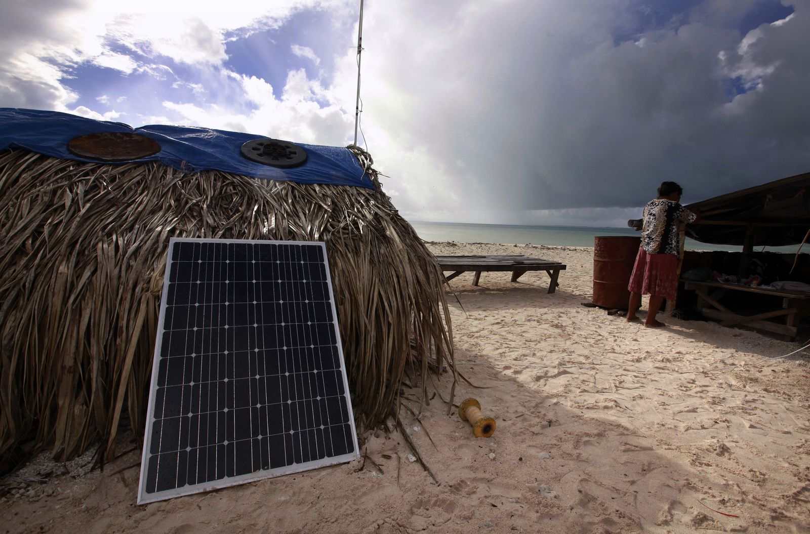 Binata Pinata checks the roof of her home as a storm approaches Bikeman islet, located off South Tarawa in the central Pacific island nation of Kiribati