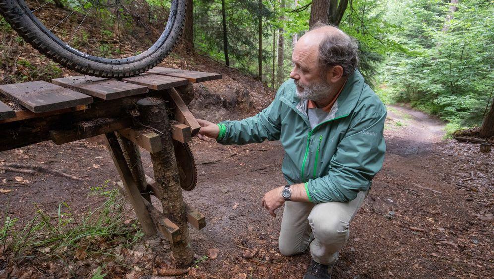 Nürnberger Reichswald: Förster Hans-Joachim Ulrich zeigt eine von Mountainbikern selbst errichtete Sprungschanze. Einige davon werden wegen der Unfallgefahr und der Schäden für Wald und Natur abgerissen.