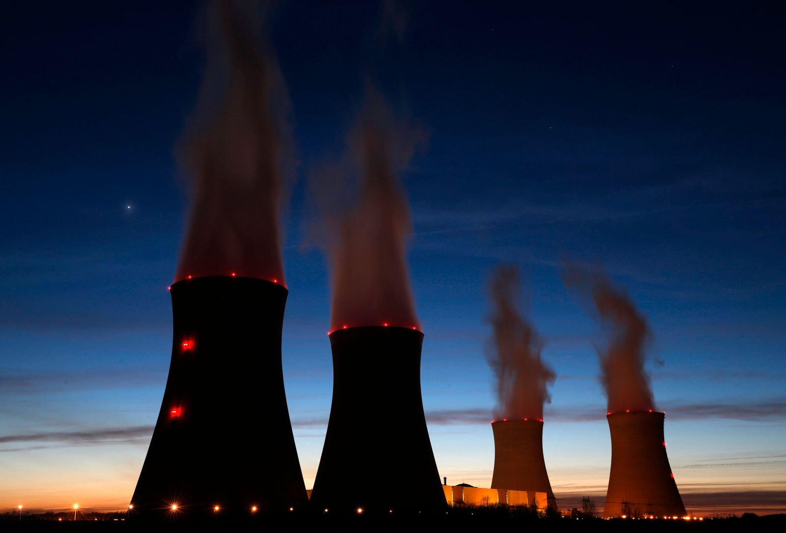 Steam rises at night from the cooling towers of the Dampierre nuclear power plant