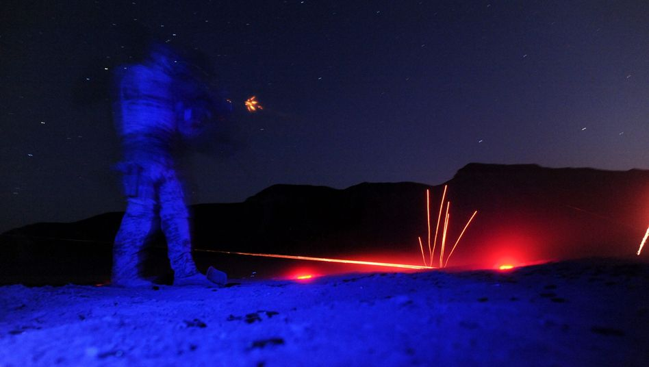 A German Bundeswehr soldier fires a gun during a night-time exercise in the district of Chahar Dara in northern Afghanistan.