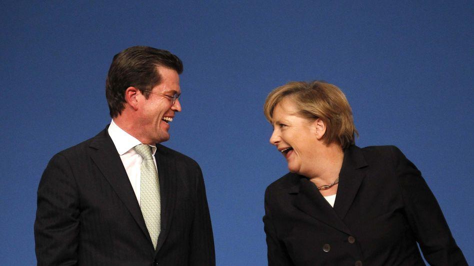 Karl-Theodor zu Guttenberg und Angela Merkel: Wer nicht sparen muss, hat Spaß