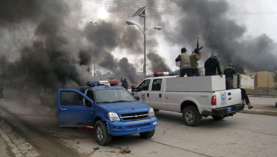 Rebellen vor brennendem Polizeiauto: Chaos in Teilen des Irak