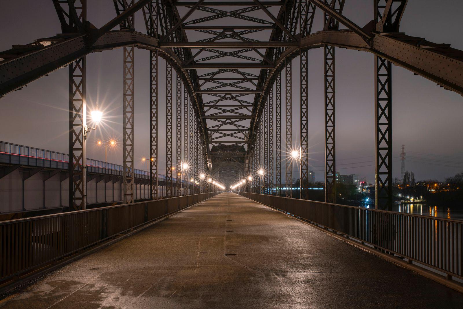 Germany, Hamburg, Diminishing perspective of Alte Harburger Elbbrucke bridge at night RJF00856