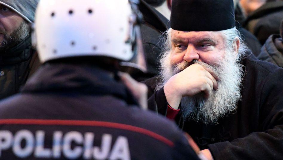 Ein Geistlicher der serbisch-orthodoxen Kirche steht vor einem Polizisten