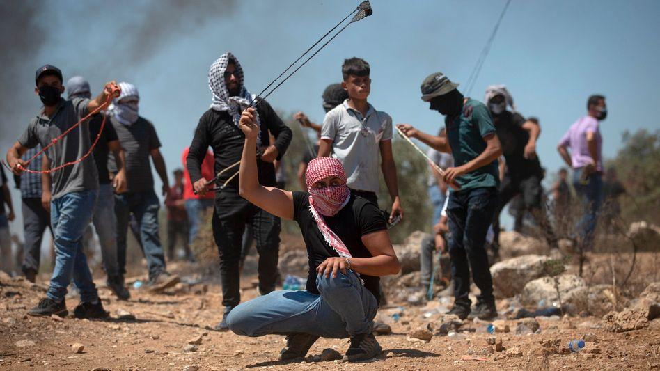 Palästinensische Demonstranten schleudern bei einer Demonstration gegen den jüdischen Siedlungsaußenposten Eviatar Steine auf israelische Sicherheitskräfte
