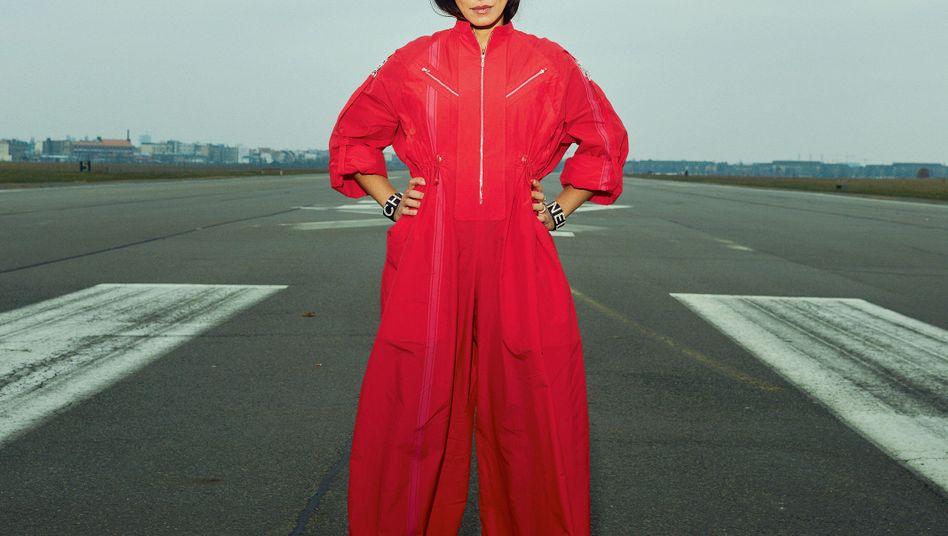 MARYAM ZAREE: Overall aus Baumwolle von Hermès, 4200 Euro; Pumps von Santoni, 490 Euro; Armreifen aus Metall und Leder mit Strassschriftzug von Chanel, 1760 Euro