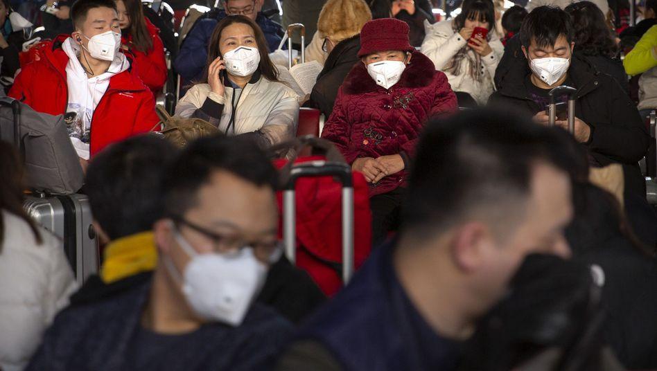 Reisende in Peking tragen einen Mundschutz gegen die Verbreitung des Coronavirus: Die Erkenntnisse der Behörden über das neuartige Virus sind noch begrenzt